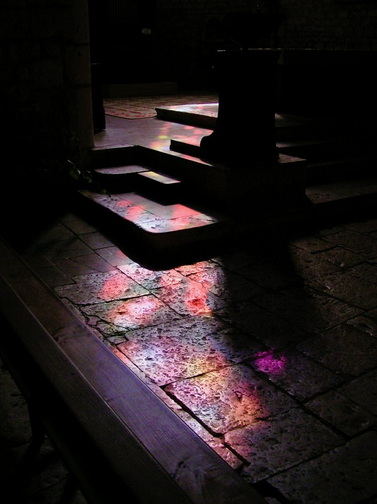 From darkness into Light--light from a stained-glass window on the dark stone floor of a medieval church in France.